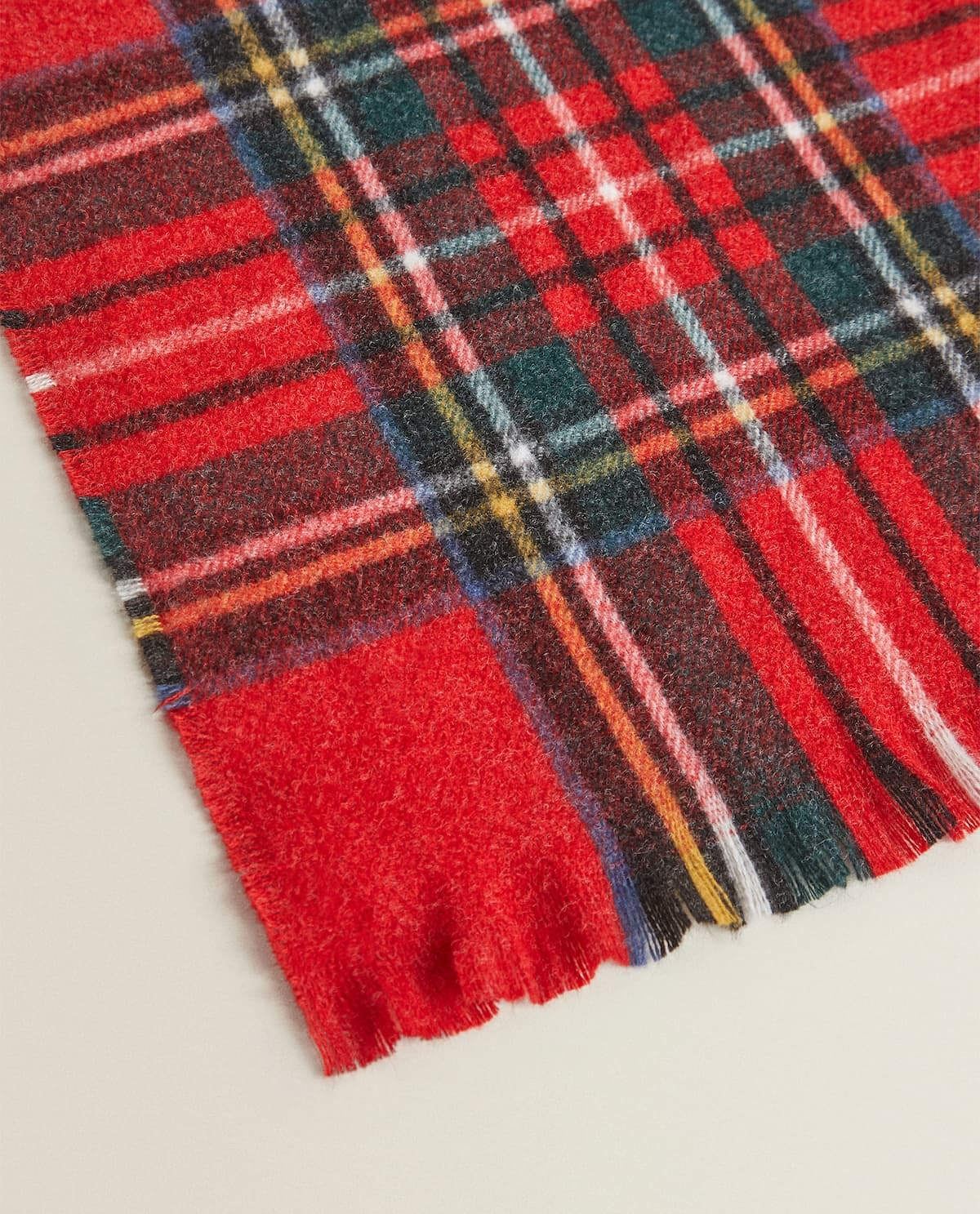 Blanket with a red background and a plaid design.  Fringed edge detail