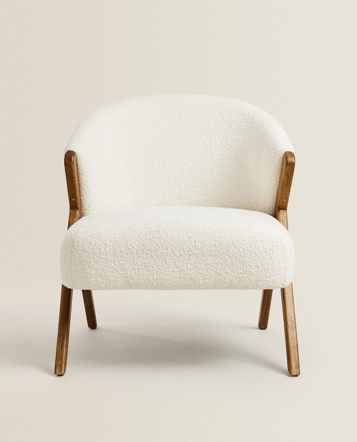 Armchair upholstered in bouclé fabric with contrasting wooden sides and legs